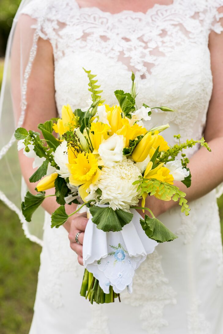 Spring green and sunshine yellow are Angela and Landon's favorite colors, so it was no surprise that they also popped up in her bouquet. Signature Florals made sure it was filled with bright flowers, including yellow tulips, yellow petunias, white lisianthus, white chrysanthemums, greenery and yellow daffodils (her favorite). Angela's great-grandmother's embroidered handkerchief gathered each of its stems together.