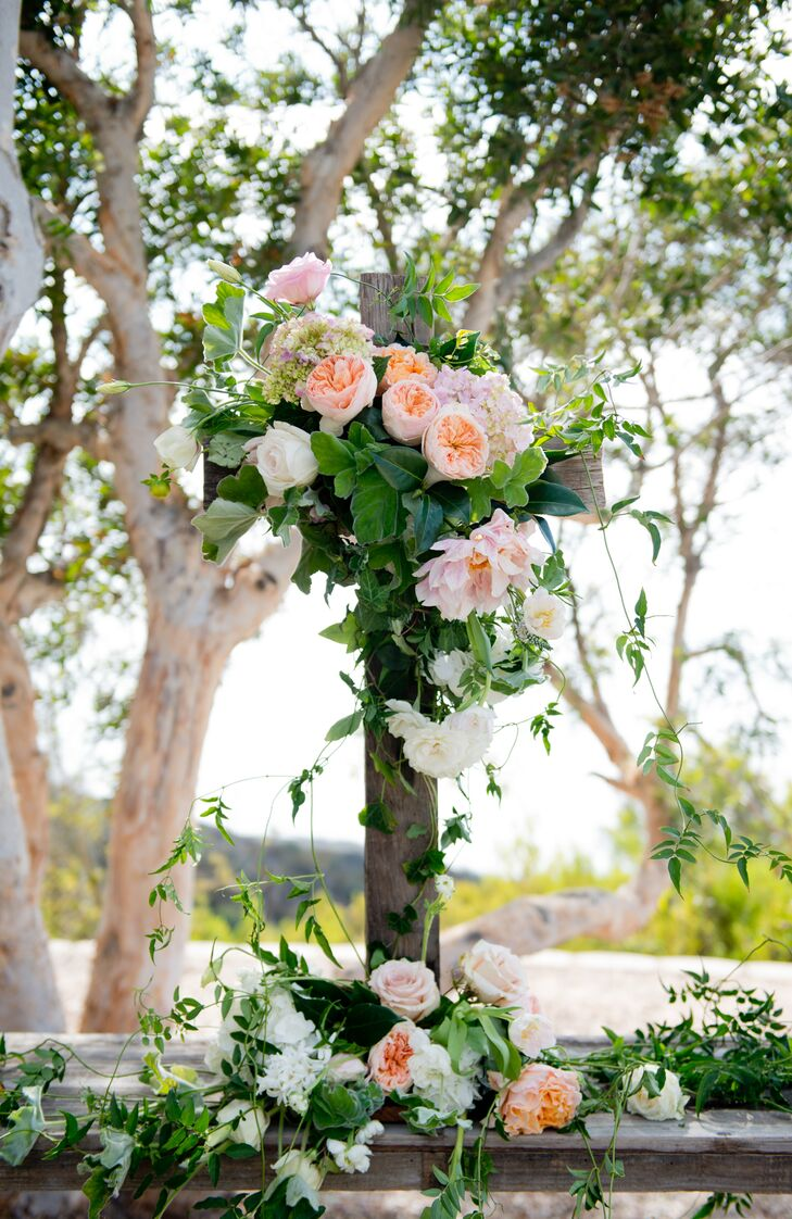 Lush greenery surrounded the ceremony, giving the area an intimate, romantic feel and required little decoration. For a subtle pop of color, the couple added a simple wooden cross as a backdrop adorned with a cascade of peach and pink garden roses and ivy.