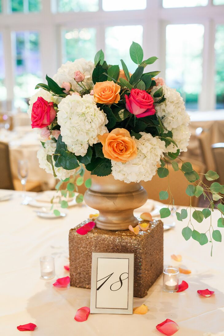 At the Hindu reception, simple low floral centerpieces in bronze urns topped each white linen-covered table.