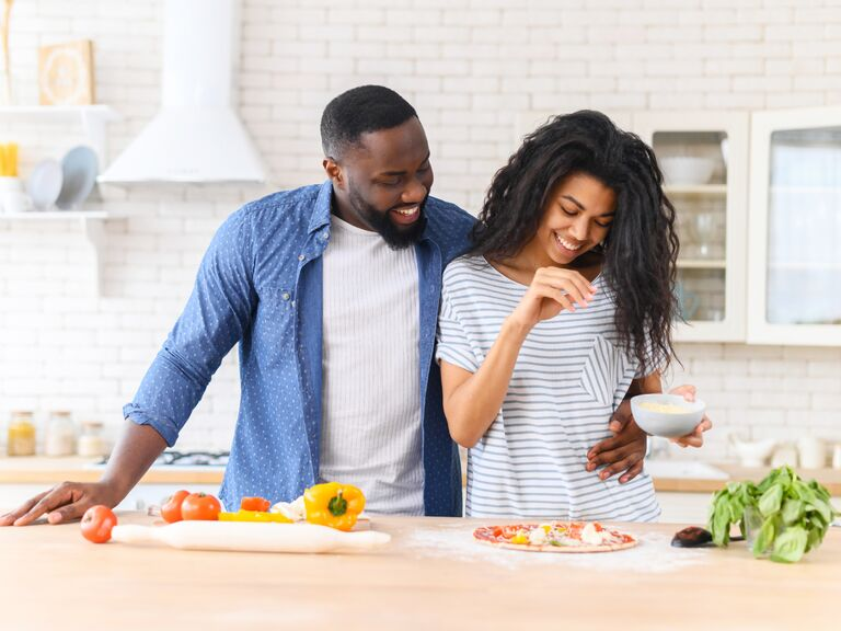 Couple smiling and cooking pizza at home together