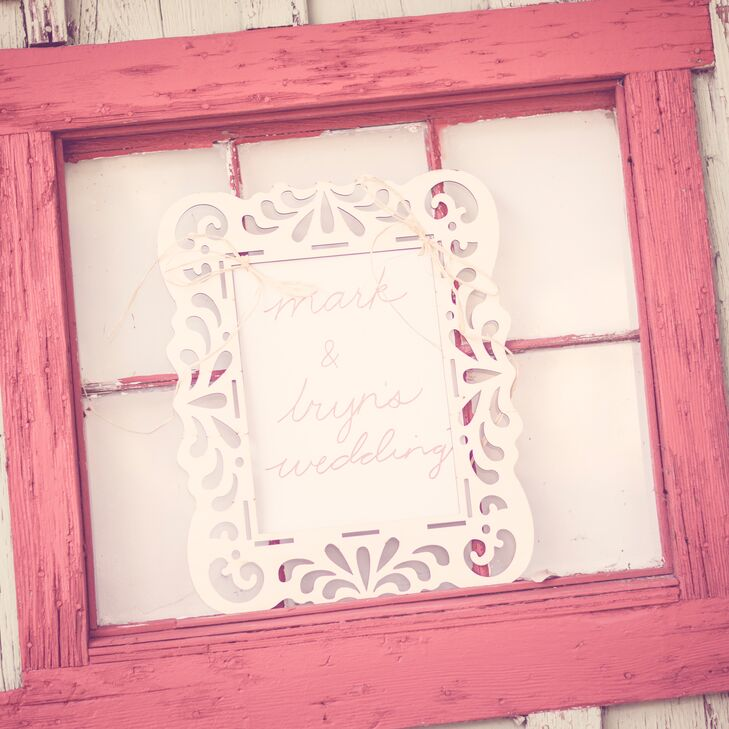 The bride and groom went for a neutral color palette to bring out the rustic feel of their outdoor wedding. The reception decor featured some coral accents, like this rustic window frame with a custom sign.