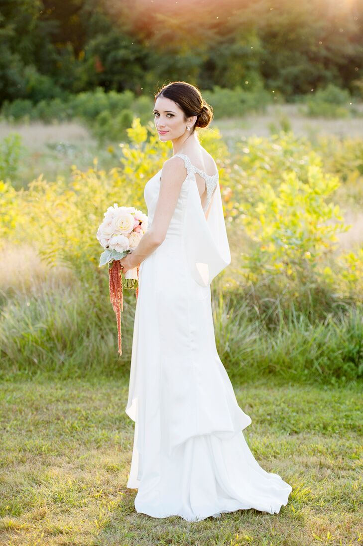 """""""I wanted our wedding to have a sort of vintage, clean, classic feel with a little bit of my bohemian spirit coming through,"""" MacKenzie says. On a trip to Mariella's Creations in Rocky Hill, Connecticut, to gather dress inspiration, she found a gown that perfectly captured her vision. The Enzoani design had timeless appeal with a classic A-line silhouette, V-neckline and subtle draping, while a silk cape and beaded details along the back gave the gown undeniable vintage flair."""