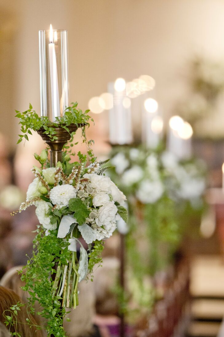 The ceremony candles were decorated with delicate greenery and bunches of white blooms like dahlias, roses and lily of the valley.