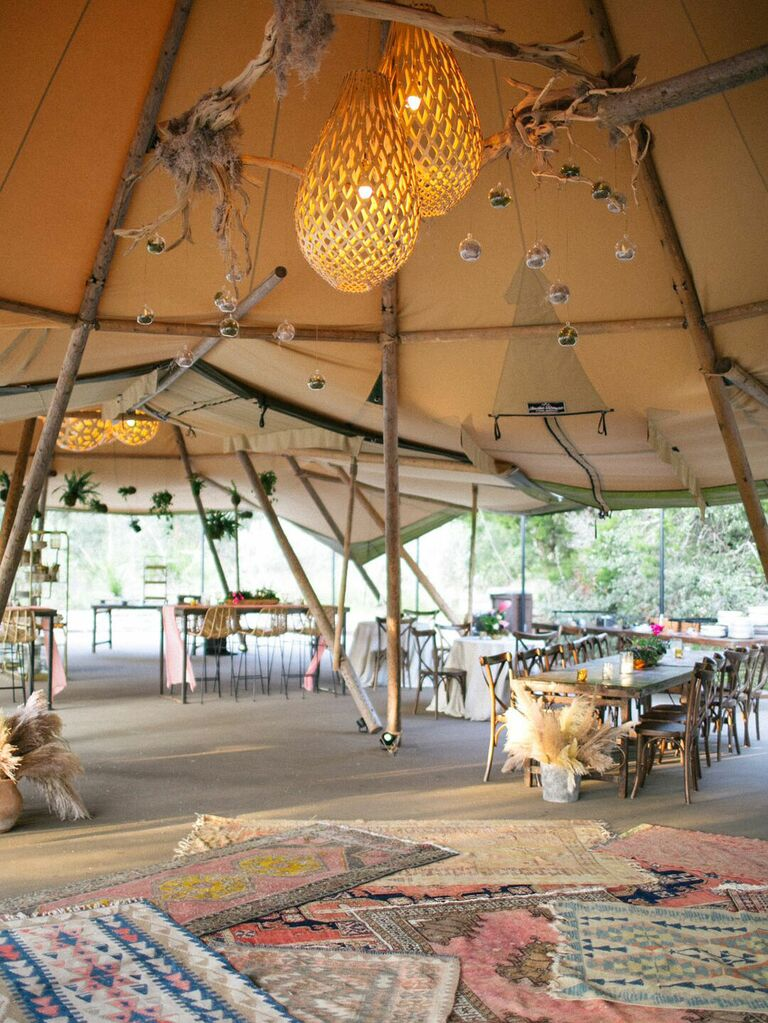 Layered boho rugs inside wedding tent with macramé lighting and clusters of branches