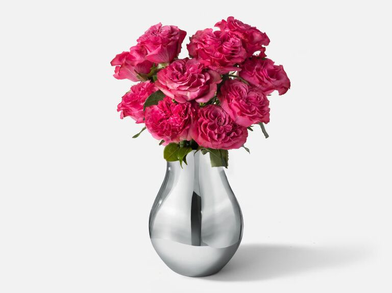 Curved stainless steel vase filled with pink roses