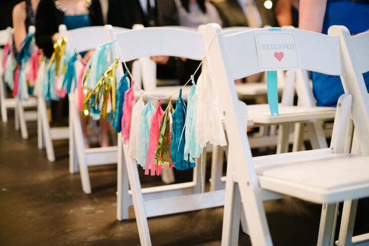 Garlands of paper tassels decorated the aisle chairs at the ceremony.