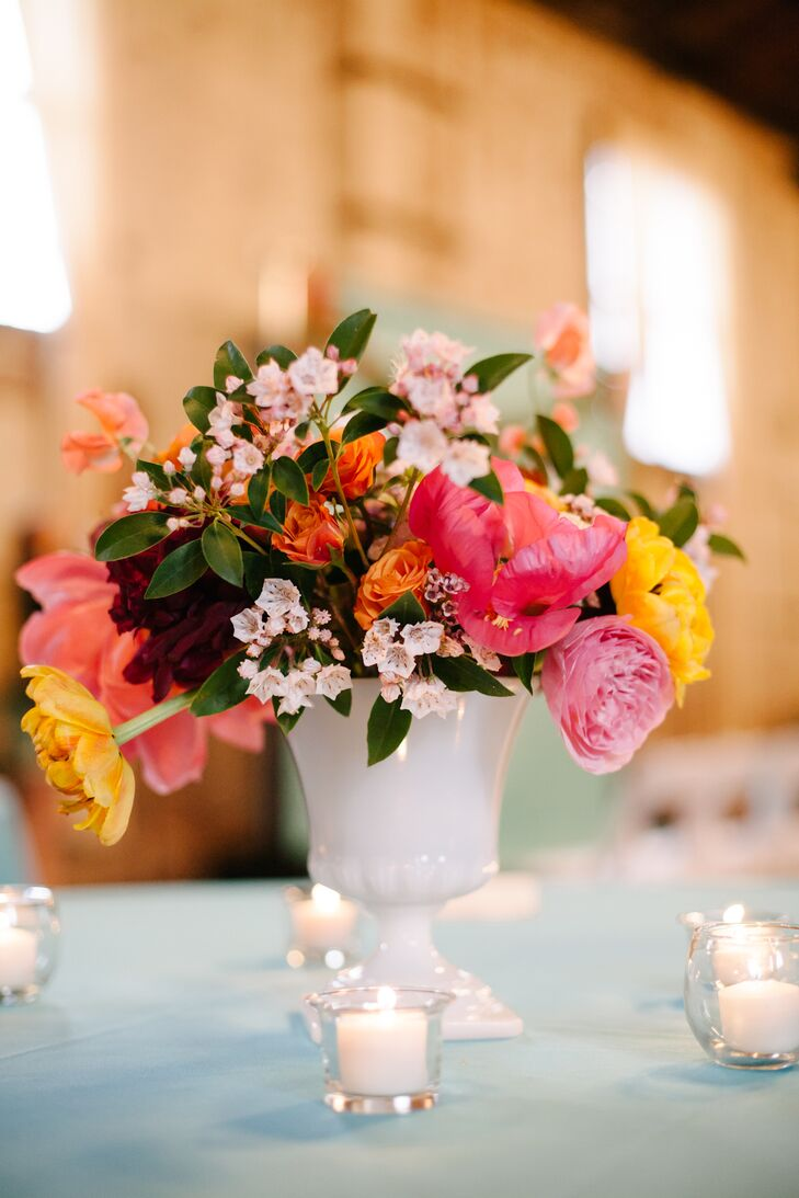 Kimberley's mother and sister helped her collect vintage milk glass vases for the centerpieces. Vibrant yellow and pink blooms added color to the arrangements.