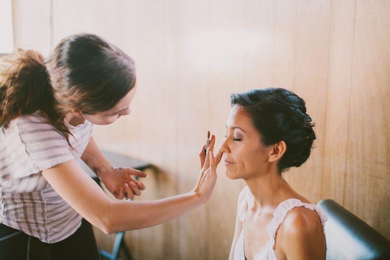 wedding makeup artist applying makeup to a bride on her wedding day