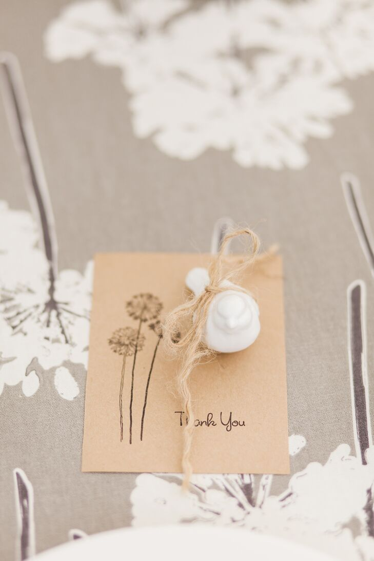 Madison found ceramic bird figurines at a home and garden store and placed one at each place setting to continue the bird theme. They rested on hand-stamped thank-you cards with dandelions to match the table linens.