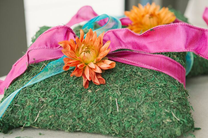 Bright orange dahlias and pink ribbon added a fresh punch of color to the mossy ring pillow.