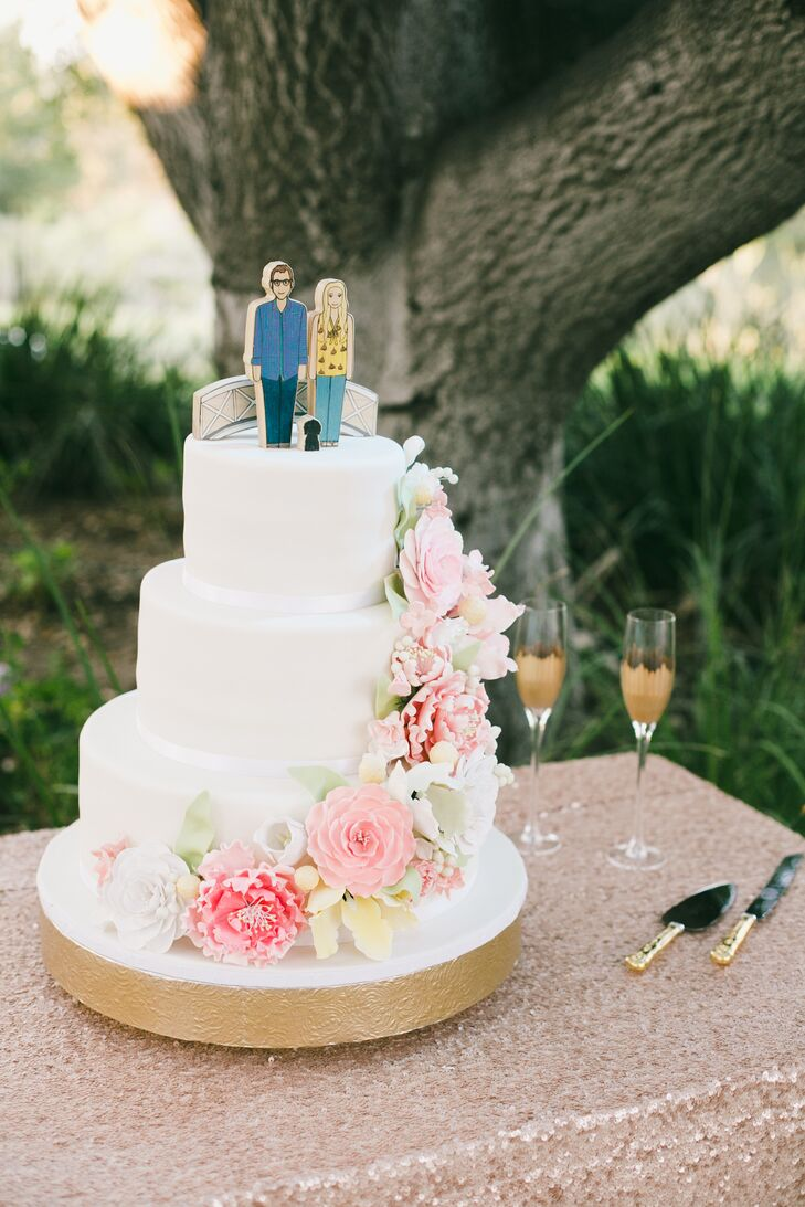The three-tier ivory wedding cake was accented from top to bottom with pink cake flowers, created by Fantasy Frostings. The cake was positioned on top of a gold stand, and the top was accented with wooden figurines of the bride, groom and their dog, who was present at their wedding.