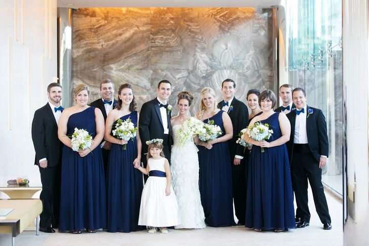 The bridesmaids wore floor-length, navy, one-shoulder gowns with ruched bodices. They each accessorized with matching Kate Spade earrings and gold bracelets.