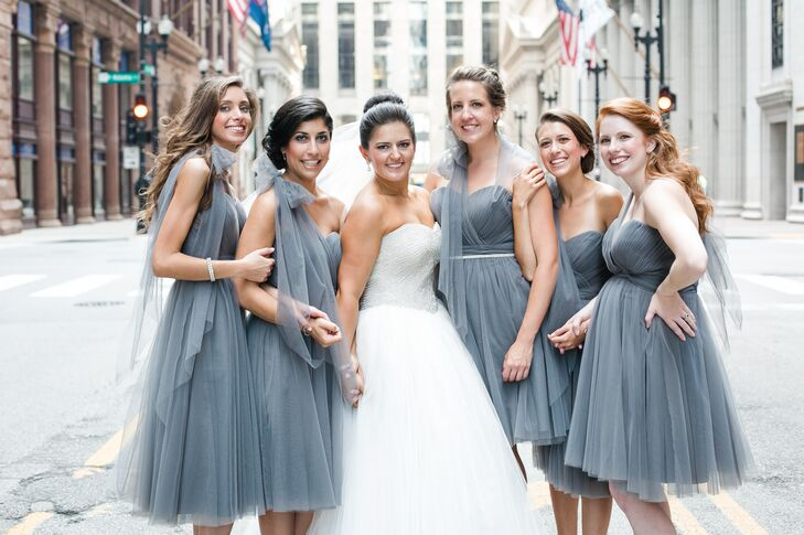 For her bridesmaids, Alyse chose Sorella Vita convertible dresses in a sophisticated shade of gray. For the ceremony, they wore the elegant, feminine dresses in a romantic one-shoulder style and then were able to change up the look for the reception. The girls accessorized with canary yellow shoes to complement the wedding's gray and yellow color scheme.