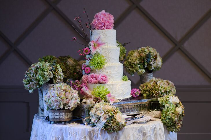 Sarah and Tom's cake design was the ideal match for the natural theme. Each tier had green dianthus, pink peonies, pink stargazer lilies or branches atop buttercream frosting, not to mention a pink hydrangea topper. To make it even more extravagant, the couple's bridesmaids placed their green hydrangea and white rose bouquets around the dessert.