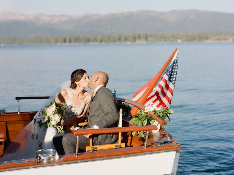 bride and groom kissing on the back of a boat with American flag