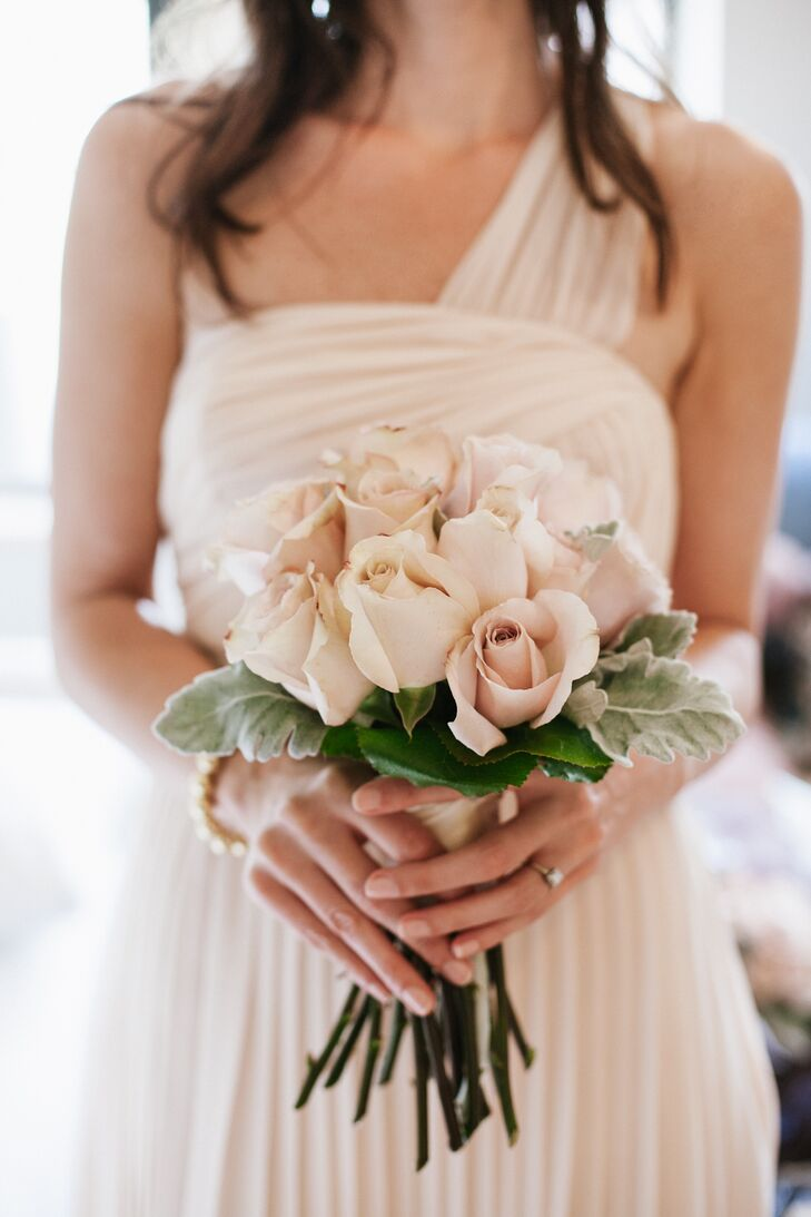 The bridesmaids bouquet mirrored the bridal bouquet with soft peach-colored roses and sage-colored greens.