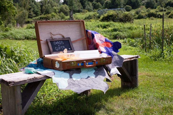 A vintage suitcase with a small chalkboard sign directed guests to where they could leave their cards and gifts for the couple.