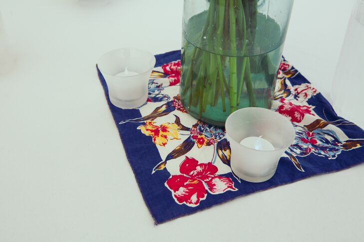 Small candle votives were placed on top of colorful floral handkerchiefs as a base for the centerpiece arrangements.