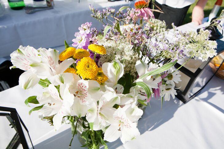 A lush, wildflower arrangements of white alstroemerias, yellow dahlias and Baby's breath made up the  centerpiece arrangements.