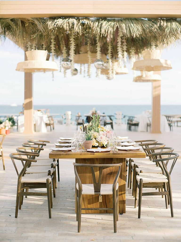 Elegant beach reception with wishbone chairs, wood table and woven chandeliers
