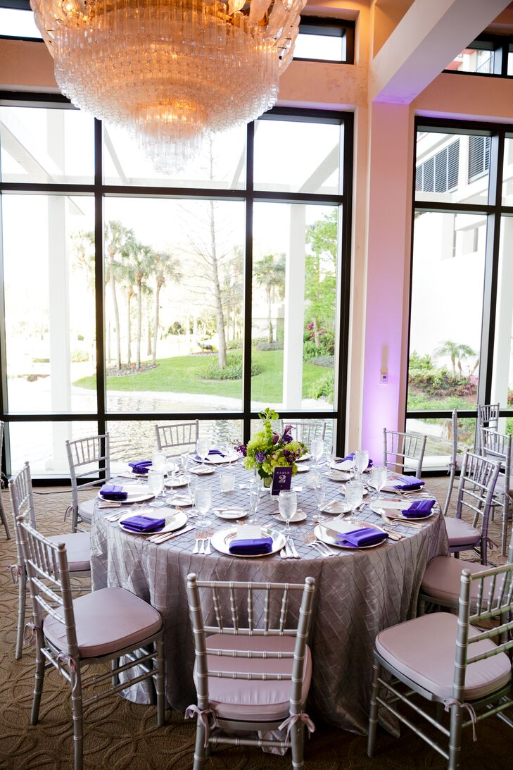 The couple decorated their reception with silver chiavari chairs, silver chargers, silver linens accented with purple napkins, bold purple table numbers and low floral centerpieces in purple and green hues.