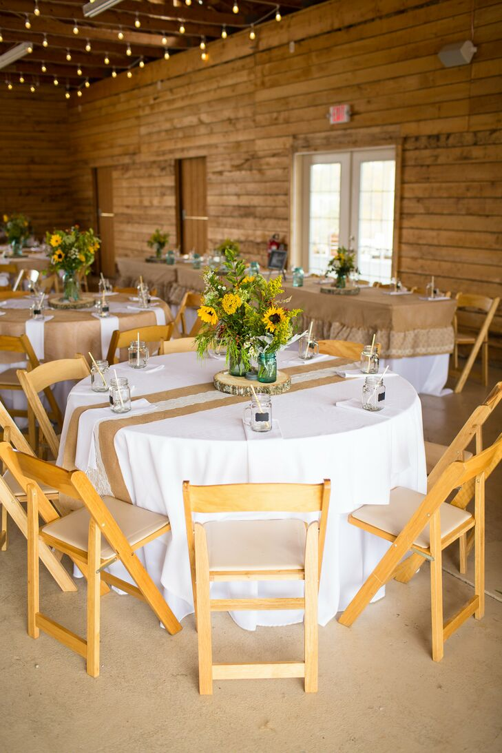 Inside the barn reception at Herot Hall Farm in Kenna, West Virginia, dining tables covered in white linens had lace and burlap draped down the middle. Centerpieces of sunflowers with greenery decorated the middle of the table, propped up on wooden slabs that went along with the interior of the barn.