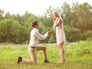 man proposing to a woman in a field
