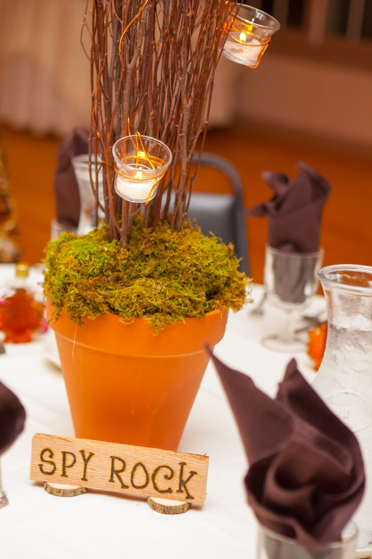Centerpieces at the Bowling Green Country Club reception consisted of branches with votive candles and moss in pots. Tables were named after some of the couple's favorite locations.