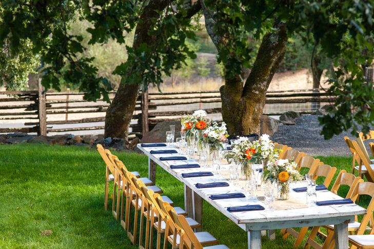 At the reception, wooden tables painted white with chairs lining the sides were decorated with blue linens and flower centerpieces.