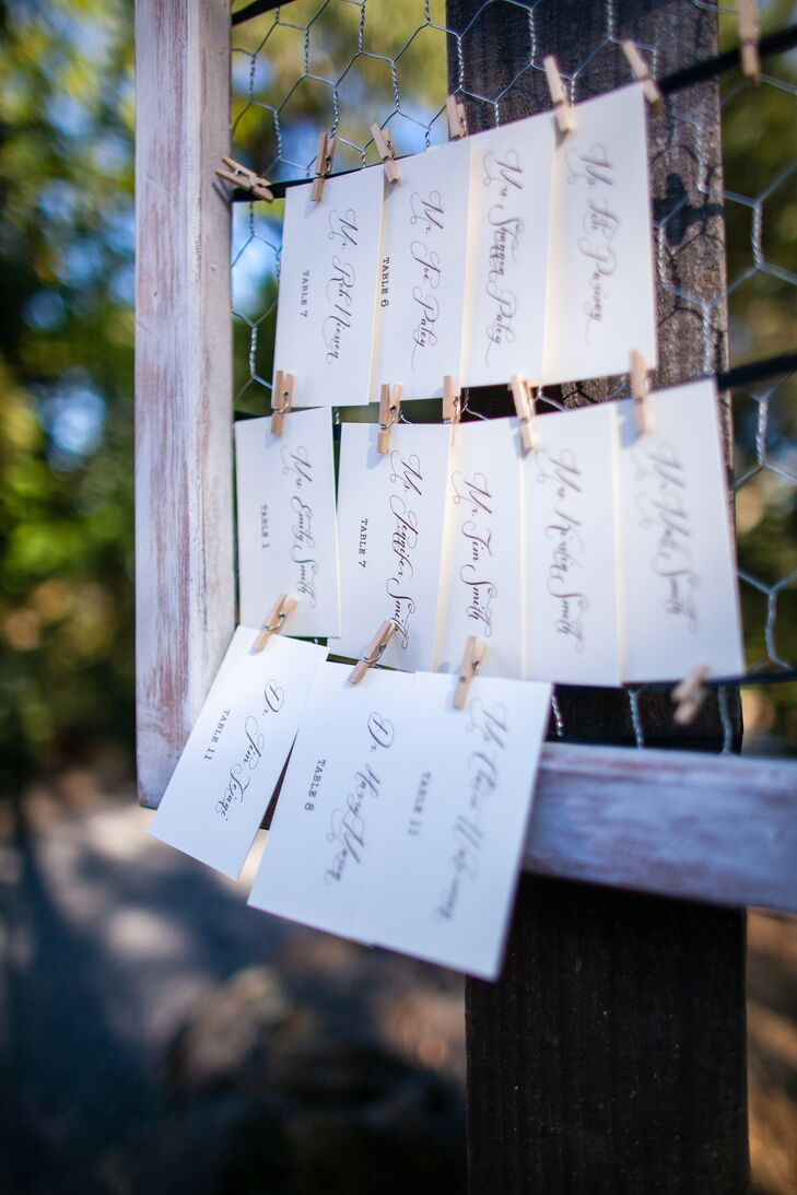 Escort cards were printed on white paper and hung by clothespins on wire attached to a wooden frame.