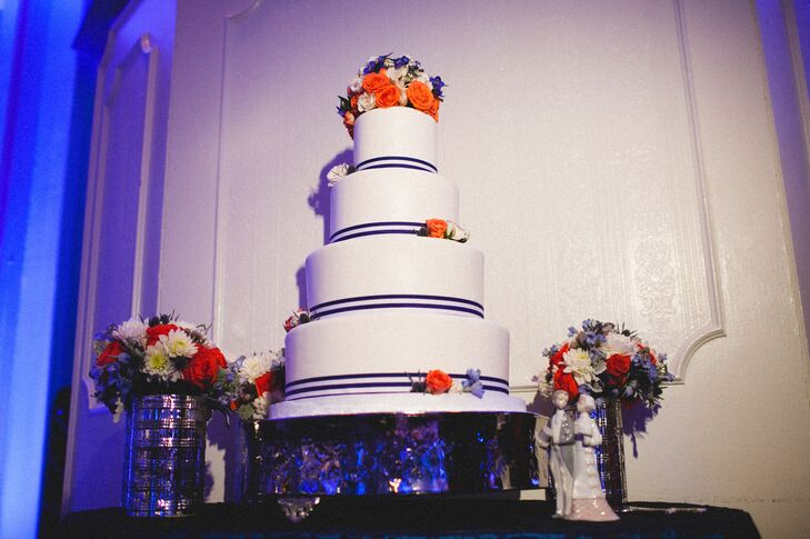 Kristen and Ken's beautiful four-tier wedding cake had white frosting and was decorated with stripes and flowers in their signature shades of navy and persimmon.
