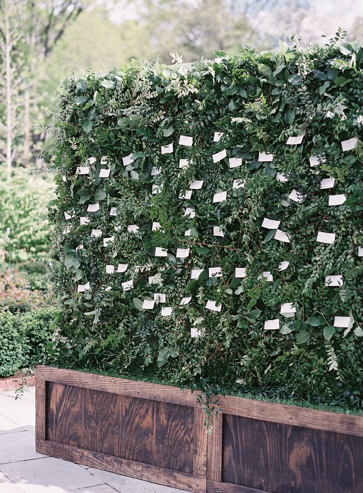"""One of my favorite pieces of decor was our display of the escort cards,"" Nina says. She and Matt created a wall of greenery to pin escort cards to. The creative use of greenery erased the dividing lines between inside and outside and enhanced the garden motif."