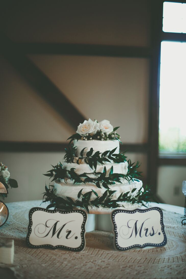 The elegant three-tier white cake was decorated in greenery.  There were two layers of carrot cake and a layer of vanilla bean with homemade raspberry jam.