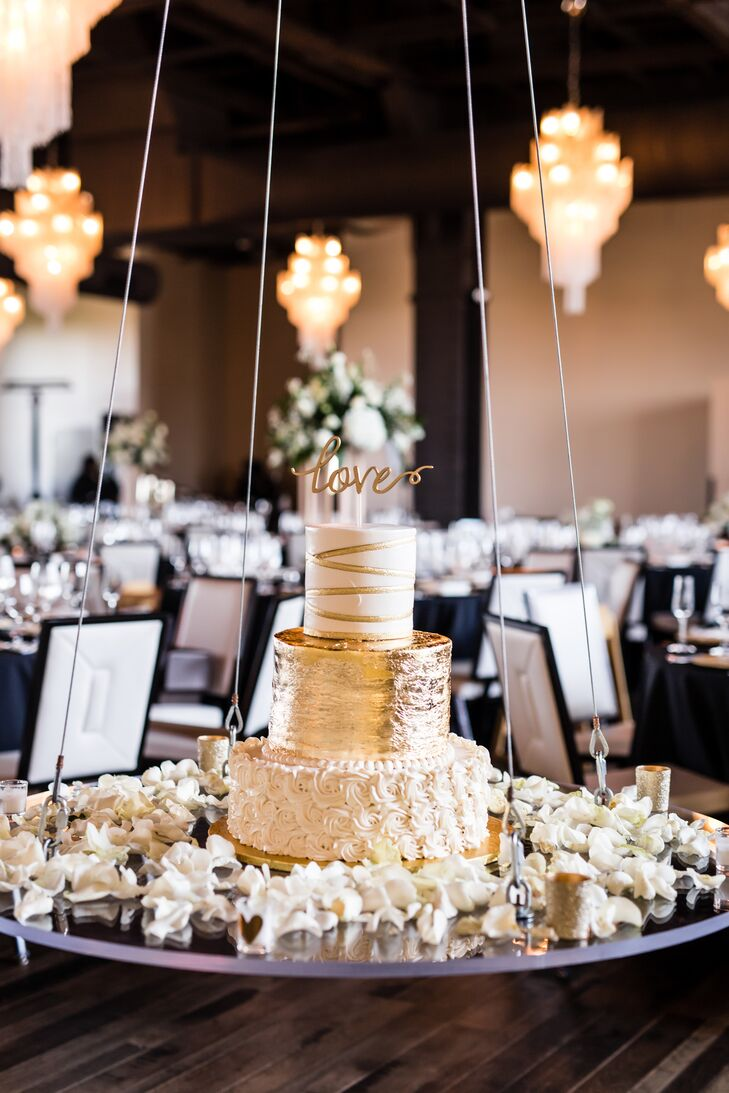 The three-tier cake was decorated in vanilla buttercream rosettes, ribbons, candy pearls and 24K gold leafing. Whitley and Carlo saved money by ordering a smaller-tier main wedding cake and serving guests sheet cake. As a fun element, the platter the cake was on was suspended from the ceiling.