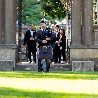 Bagpipe ceremony processional at outdoor Irish wedding