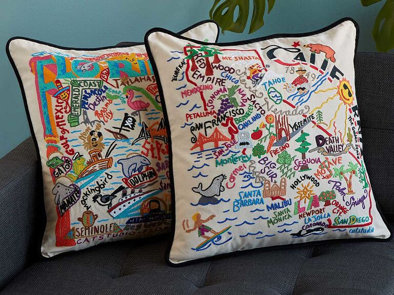 Two embroidered throw pillows representing California and Florida