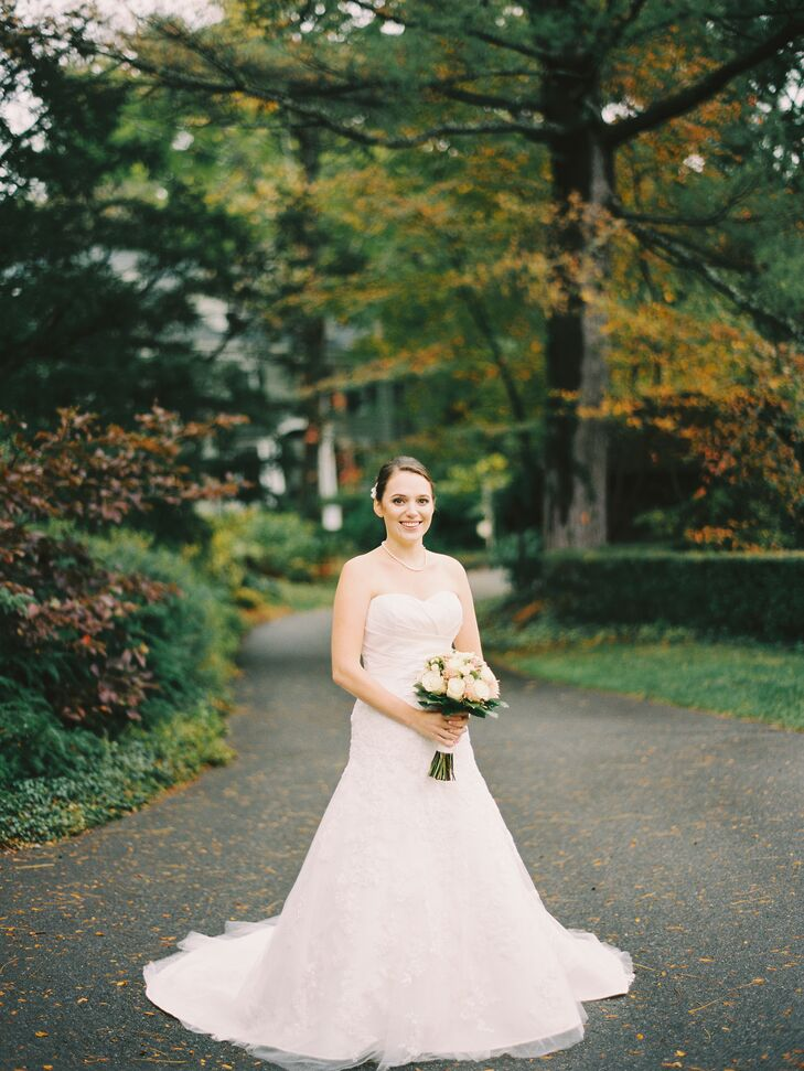 """My wedding dress was a strapless fit-and-flare gown with a sweetheart neckline,"" says Emily. ""It was pleated at the top with lace on the skirt portion.  I wore simple white satin flats and my mom's cathedral length veil."""