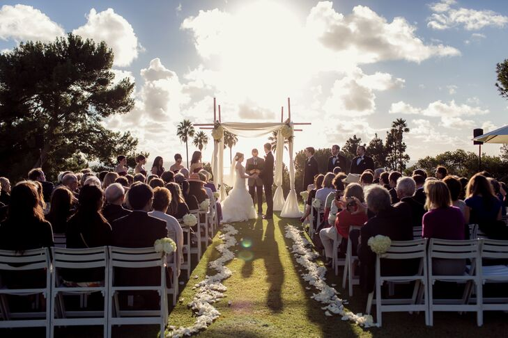 The aisle was lined in a zig zag of ivory rose petal with matching bouquets hung on chairs throughout. The tall arbor was made of criss-crossed bamboo and draped in a delicate sheer white fabric.