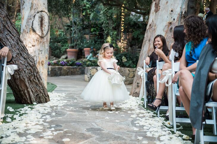Emma, the flower girl, wore a fluffy white gown with a black satin waist band to match the day's simple black-and-white theme.