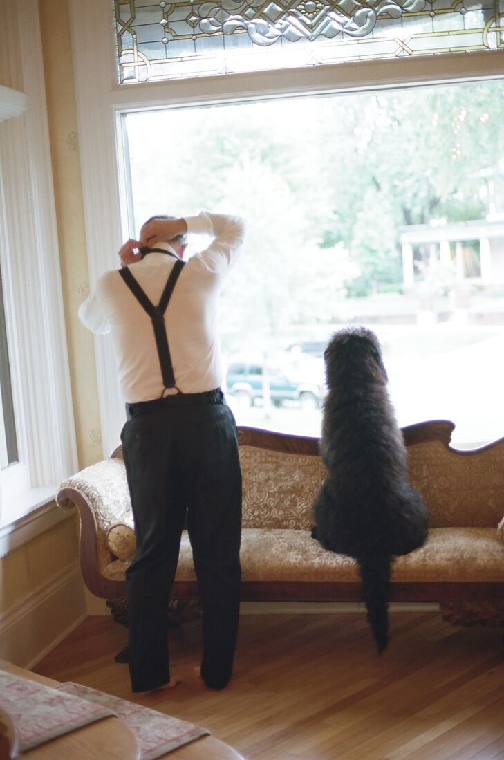The groom, in a Heimie's Haberdashery tuxedo, gets ready while the couple's sweet dog keeps him company.