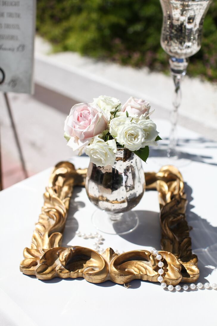 The reception tables were decorated with vintage gold picture frames and strings of pearls to match the vintage theme of the wedding. In the center of each frame was a silver mercury-glass vase filled with white and blush roses to add a pop of the wedding colors into the otherwise glam decor.