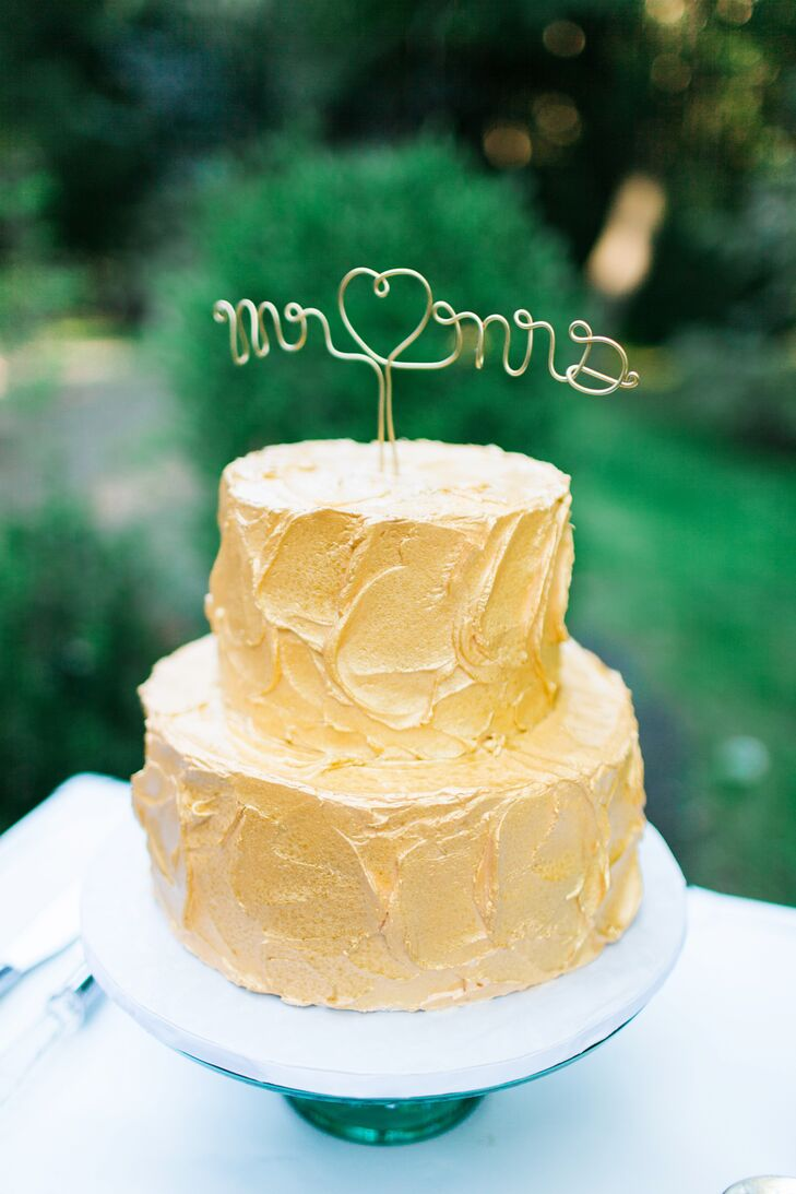 "A gold cursive ""Mr. & Mrs."" cake topper stood on top of the two-tier gold-frosted cake."