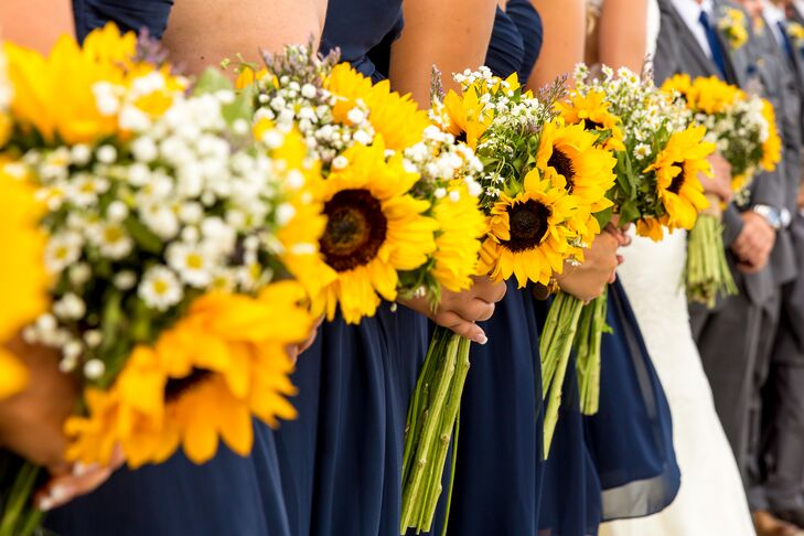 Think Flowers created all the stunning sunflower arrangements for the rustic wedding. Kerry and her bridesmaids carried identical bouquets, including long-stemmed sunflowers and baby's breath.