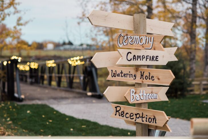 To help their guests find their way around the expansive property, Julia and Matthew handcrafted wooden directional signs that pointed to the Leduc, Alberta, site of the ceremony, reception and after-party activities.