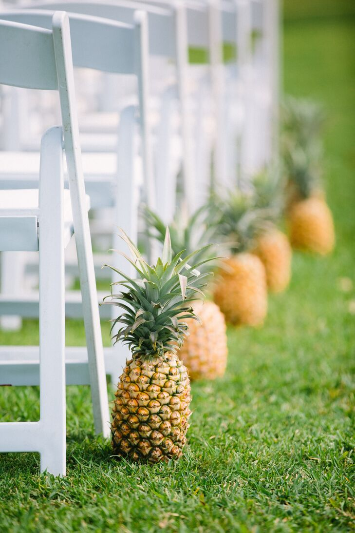 "Instead of flowers, Olivia chose to line the aisle with fresh, locally grown pineapples. ""Pineapples fit perfectly into the theme since they are symbol of hospitality in the South and are grown locally in Hawaii,"" Olivia says."