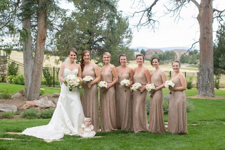 The bridesmaids wore floor-length, dusted-rose beaded gowns. Together, they carried bouquets that bound together the same arrangements used by the mother and grandmother of the bride with ivory silk ribbons.