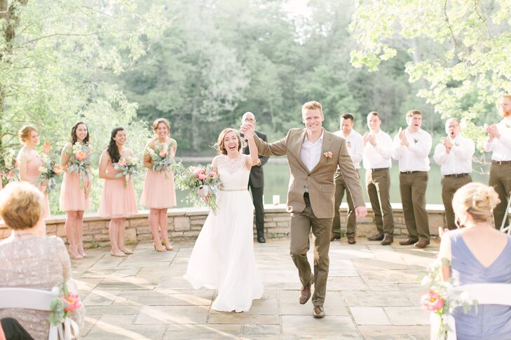 Anna picked out a Sarah Seven ivory wedding dress with a high illusion neckline detailed with lace and a thin crystal belt that wrapped around the waistline. Thomas walked next to her during their recessional, who wore a brown jacket with matching brown pants.