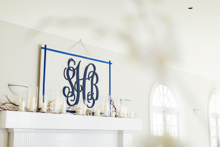 The mantle was decorated with driftwood, plump white candles and an upholstered sign that featured the couple's monogram.