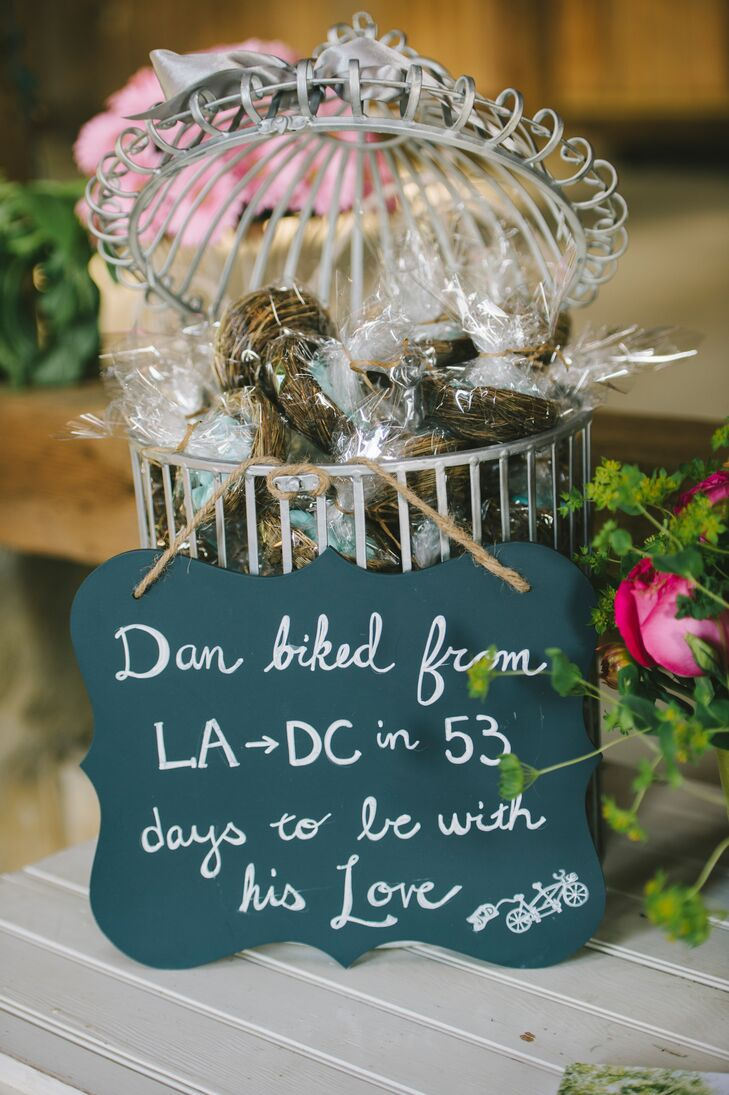 Guests took blue Jordan almonds inside miniature bird nests as wedding favors, placed inside a white birdcage. A black chalkboard sign hung from the display, which showcased Dan's love for Jess through one of their memories.