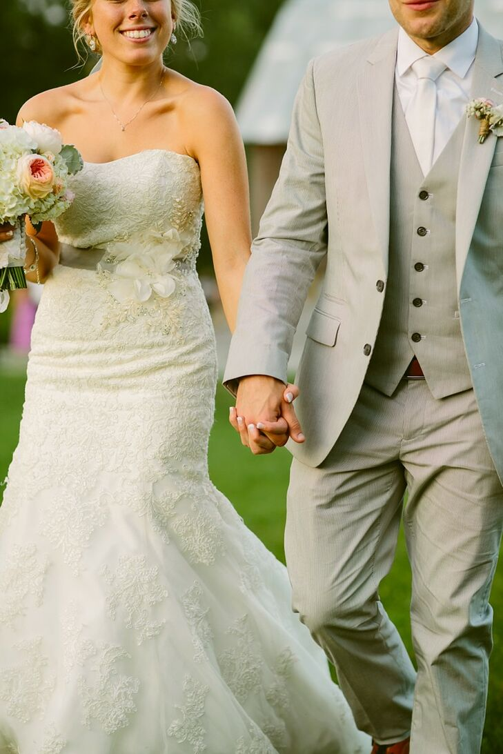 Erin's strapless, lace, fit and flare wedding dress had a small cluster of elegant lace flowers on the side that fell over her gray bridal sash to stand out from the fabric of the dress.